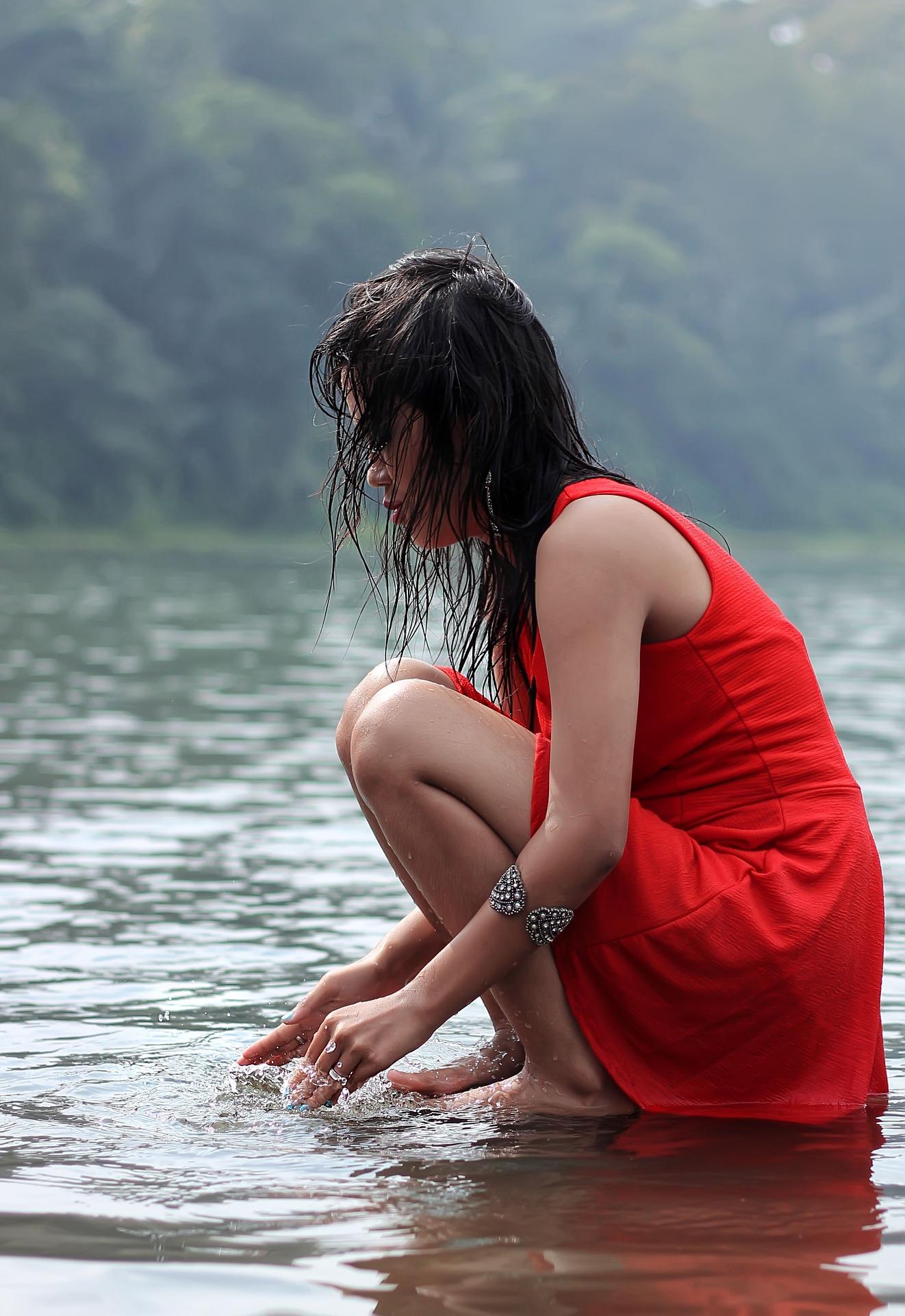 Mulher refletindo enquanto brinca na água - para o texto O Feminino como Arauto do Sentimento