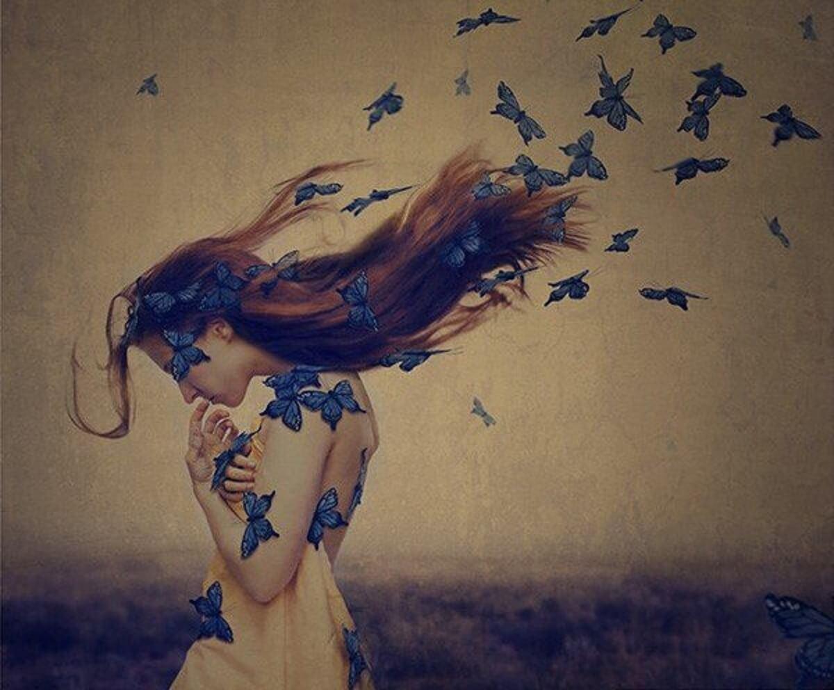 Mulher cabisbaixa cercada por borboletas