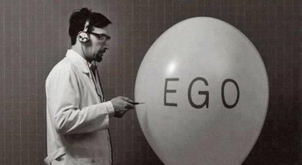 """Homem prestes a furar um balão escrito """"Ego"""", demonstrando o quão frágil é o nosso ego. Vale também lembrar que não podemos confundir """"ego"""" de jung e """"ego"""" de """"egoísta"""" por exemplo."""