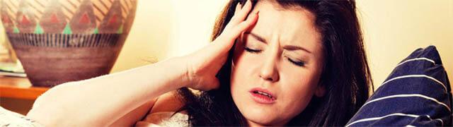 Mulher com dor de cabeça como sintoma de uma doença psicossomática